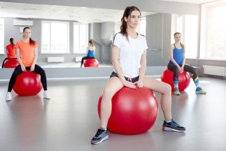 ישיבה זקופה על כדור פיזיו מחזקת את רצפת האגן. צילום: שאטרסטוק